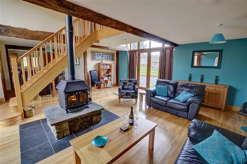 The spacious living room with central woodburner